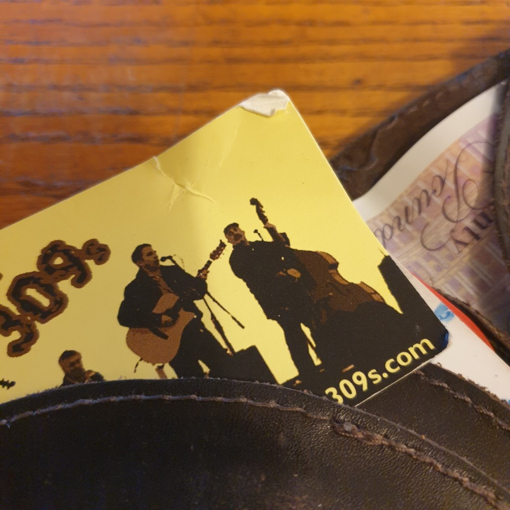 The 309s band business card, damaged from being stored in a back-pocket wallet or pocketbook