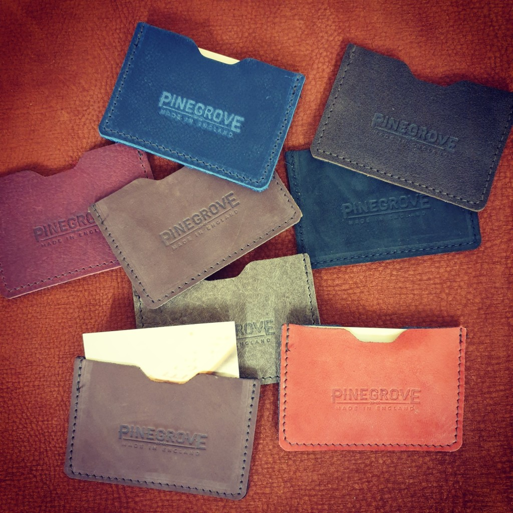 A number of Pinegrove Leather business card wallet sleeves, scattered around, with business cards